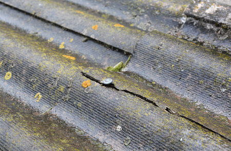 Asbestos roof crack. Old house asbestos roof with damage crack