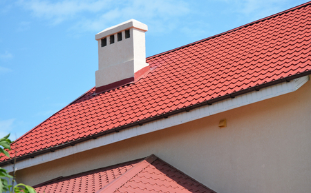 Metal house roof with chimney and soffit boards.