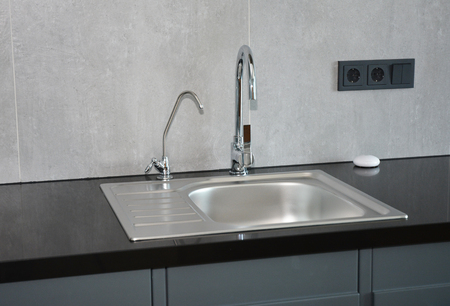 Modern kitchen with faucet and metal kitchen sink and outlets. Banco de Imagens