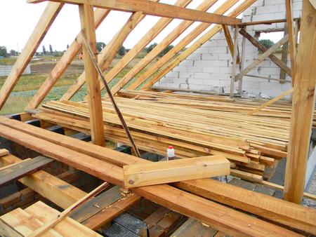 Niewykończone wiązary konstrukcyjne dachów domów, tarcica.