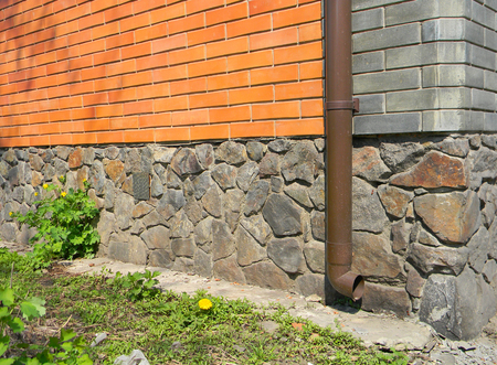 Roof gutter downspout pipe  with brick house foundation wall without drainage. Wet foundation.
