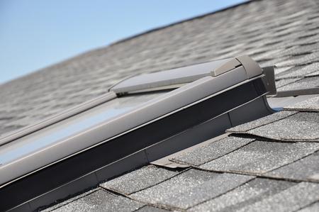 Skylight window installation details on house rooftop.