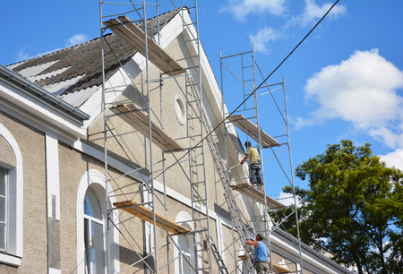 Kijów, Ukraina - 27 grudnia 2018: Wykonawcy tynkowanie elewacji domu na zewnątrz. Malowanie i tynkowanie ścian rusztowania zewnętrznego domu z naprawą dachu azbestowego.