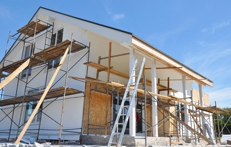 House renovation with wall insulation, plastering, paiting walls. House construction with scaffolding outdoor.