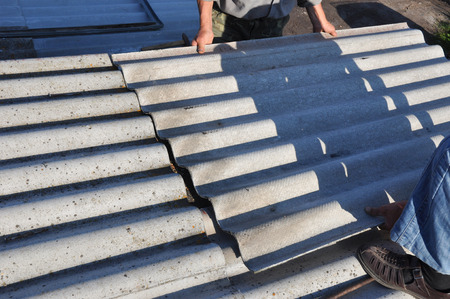 Roofers repair roof and remove asbestos old roof tiles. Roofing construction. Stock Photo