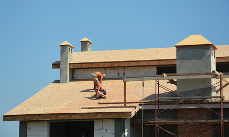 Roofing construction works by roofing contractors. Roofers preparing house roof for asphalt shingles installation. Stock Photo