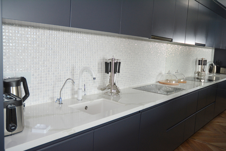 Modern kitchen with mosaic tiles, faucet, kitchen hood, mirror, oven.