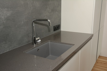 Black kitchen sink and Tap water in the kitchen. Modern kitchen metal faucet and  kitchen sink.