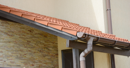Clay tiled house roof with rain gutter under entrance home door.