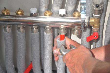 Stralende vloerverwarming installatie. Repareer vloerverwarmingssysteem met geïsoleerde metalen buizen. Stockfoto