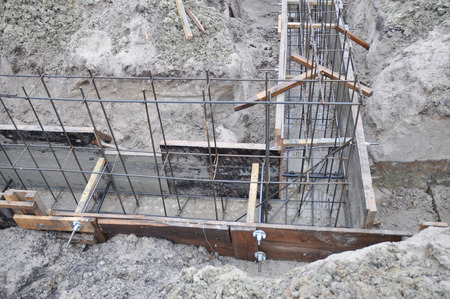 Building T-Shaped Concrete House Foundation with Slabs and iron Bars.
