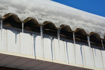 Asbestos house roof covered snow with icicles