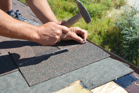 Roofing contractor installing roof tiles, asphalt shingles with hammer and nails. Roofing construction.