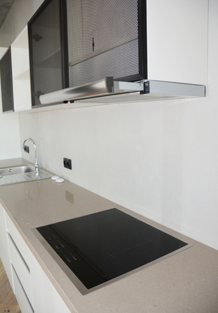 Island hood. Modern kitchen with electric oven, metal faucet, ceramic kitchen sink, electic stove and  kitchen hood with pipe. Banco de Imagens