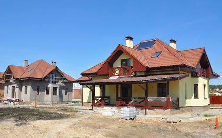 House under construction. House construction site with clay roof, lightning rod, solar water heater panels, attic skylight windows, roof lightning protection.