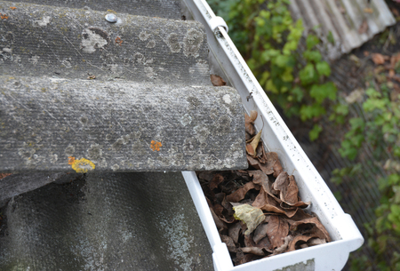 Clean gutters. Gutter Leaf Removal. Roof gutter with fallen leaves. Rain gutter cleaning photo. Stock Photo