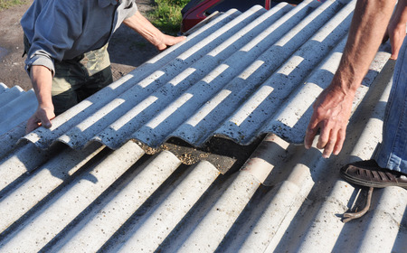 Risks of Asbestos Roofs, Asbestos Roof Removal. Asbestos removal roof works. House with old, danger asbestos roof tiles repair. Stock Photo