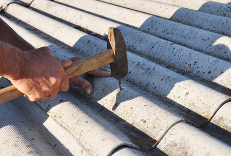 Asbestos roof tiles installation by roofer. House with old, danger asbestos roof tiles repair.