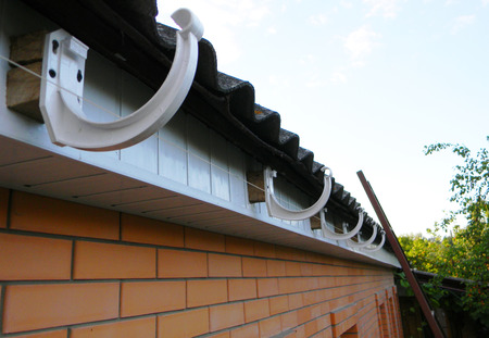 Roof gutter holders installation. House rain gutter holders installing Zdjęcie Seryjne