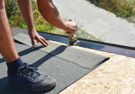 Roofer contractor gluing waterproof membrane on wooden roof top surface with brush and black bitumen  spray on tar before installing asphalt shingles. Reklamní fotografie