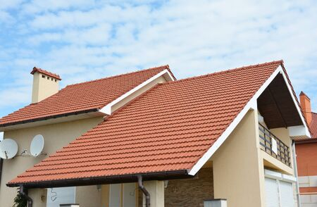 Modernes Haus mit rotem Lehmdach, Balkon, Dachrinnen, Schornstein. Tal- und Giebeldachart.