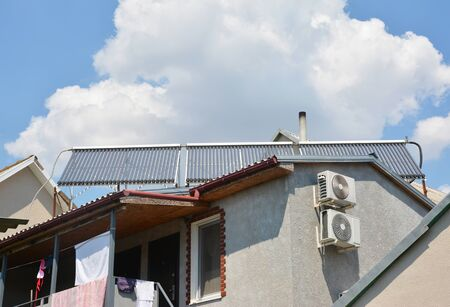 Solar water heater on house roof top with gutter, balcony air duct and chimney