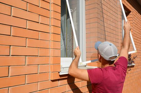 Mosquito wire screen installation. Worker installing mosquito wire screen on house window to protect from insects. Stock Photo