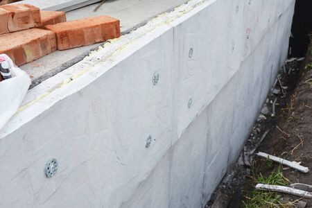 Foundation insulation. House foundation wall construction with foam insulation, damp proof, water proof layers.