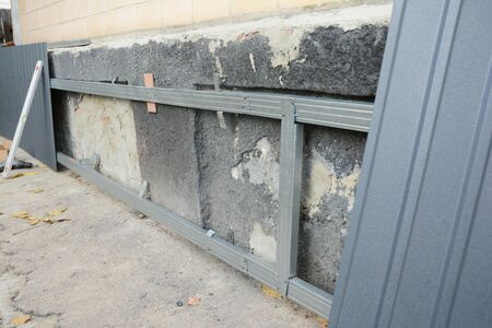 House foundation wall repair,  renovation  with installing metal sheets on metal frame for waterproofing and protect from rain wetness. Stock Photo - 126963811