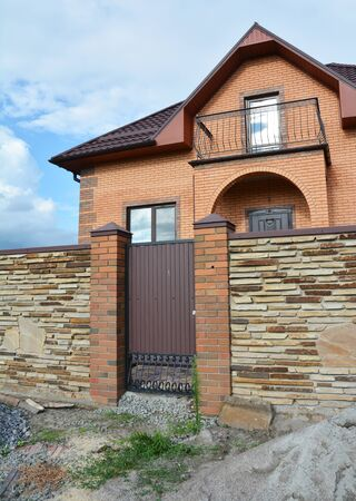 Luxury modern brick house under construction with stone fence and metal entrance door Foto de archivo - 129213395