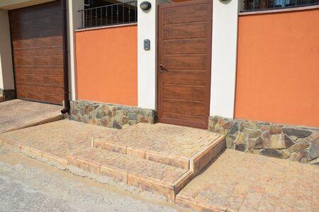 House entrance door with pavement, door bell, security camera, garage door Foto de archivo - 129213541