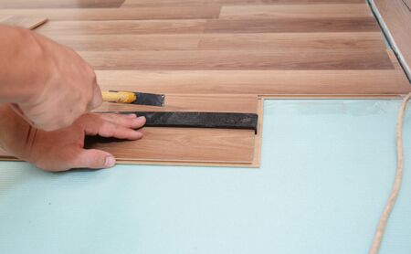 Worker Installing Wooden Laminate Flooring with Tools