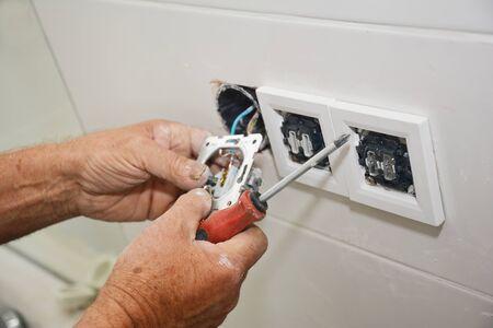 Elektricien repareren en installeren stopcontact, stopcontact Stockfoto