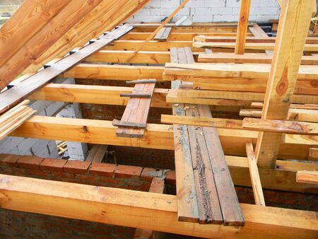Unfinished attic house roofing construction trusses, wooden beams, eaves, timber.  House roof wooden frame construction.