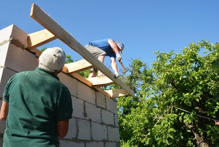 Roofers installing wooden beams, eaves, trusses on house rooftop. Roofing construction Stock Photo