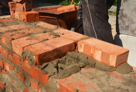 Bricklaying hhouse wall. Masonry Techniques. Bricklayers hands in masonry gloves bricklaying photo.