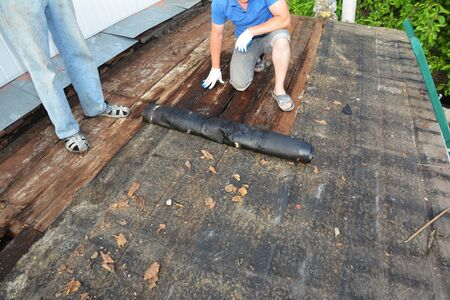 Roofers roof repair and renovation. Old house roof with bad wet wooden beams and  wet roock wool insulation material. Roofing construction