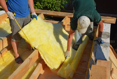Roofers Repair and Installing House Roof Thermal Insuation with Mineral Wool, Roofing Construction Stock Photo
