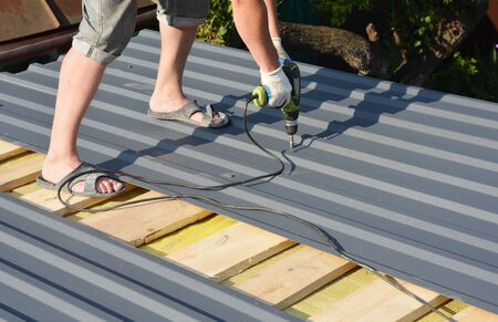 Roofing Construction. Roofer with crew gun installing  lightweight metal roof tiles roofing  construction on house roofing construction
