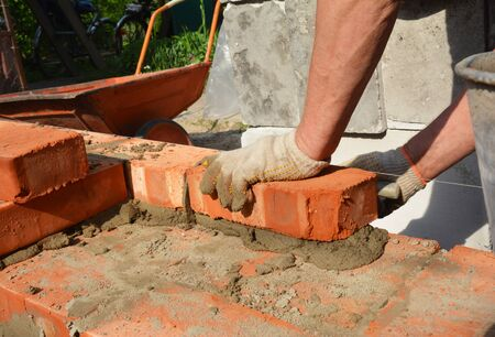 Bricklayers hands in masonry gloves bricklaying new house wall. Bricklaying house wall