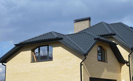 Construction de toiture en tuiles de céramique de maison de vallée et de pignon avec canalisation de gouttière. Maison en brique avec problème de construction de toiture à pignon et système de canalisation de gouttière de toit.