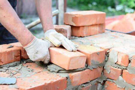Bricklaying house wall, masonry. Bricklayer hands in masonry gloves bricklaying house wall. Stock Photo