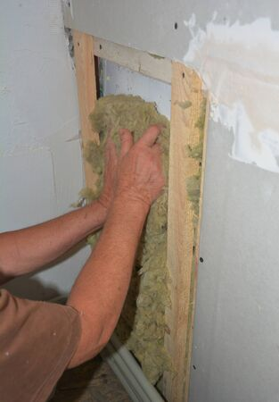 Bad example of indoor house fiberglass insulation without glowes. Worker hands insulating house drywall with rock wool