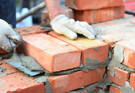 Bricklayer hands in masonry gloves with trowel laying bricks house wall.