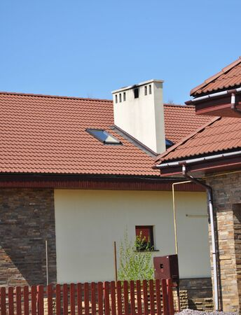 House rooftop with attic skylight window, roof gutter,  and dirty chimney Stock Photo