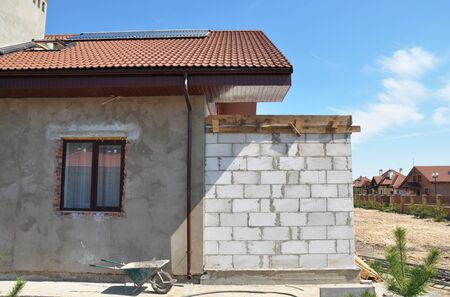 House under construction with attic skylight window, solar water heating system, roof gutter, paint and plastering walls.