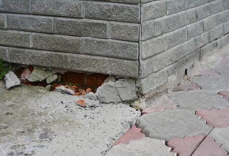 Poorly constructed foundation of the house. Ashlar facade bricks are broken damaging the foundation.