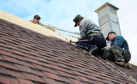 KYIV, UKRAINE - MARCH, 29, 2020: Roofer contractors are installing dimensional asphalt shingles from bottom up on the rooftop with a chimney.