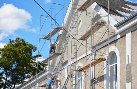 Building contractors on scaffoldings are applying stucco finish, coating and plastering the facade wall of the house.