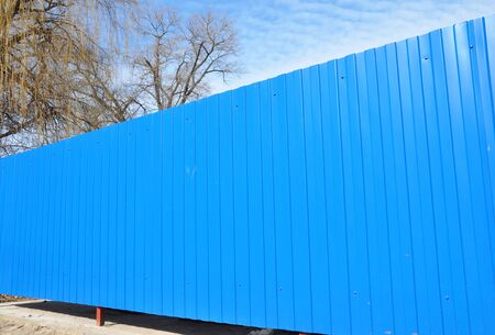Blue metal fence panels installed without any foundation using metal fence posts and frame.